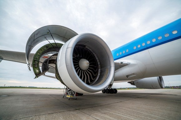 A jet engine on the tarmac, open for inspection.