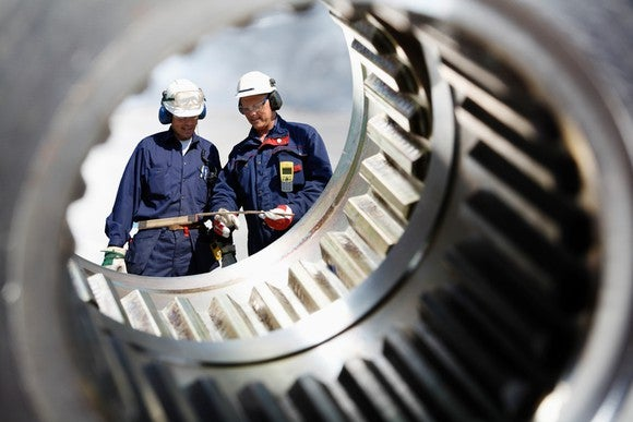 Two workers seen through a metal casing.