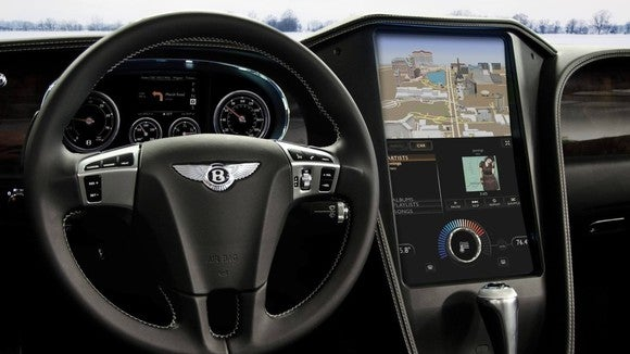 The cockpit of a Bentley car, including the steering wheel and computer screen.