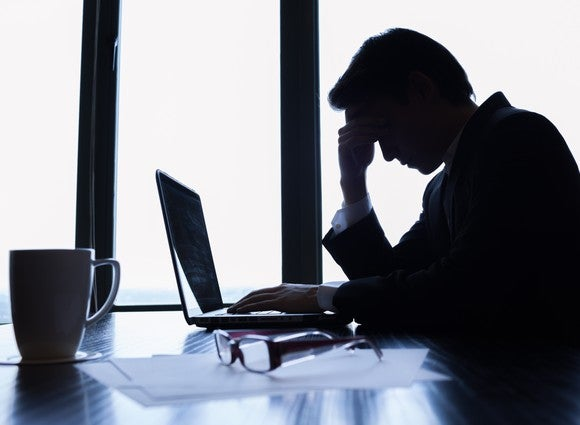 Businessman in shadow with his hand on his forehead while in front of a laptop