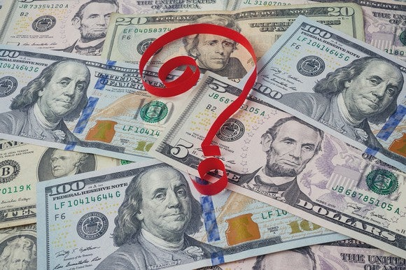 Red ribbon forming question mark on top of cash spread out on surface