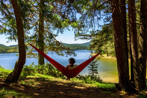 A woman sitting in a hammock hung between two trees looking over a lake.
