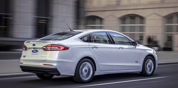 A rear three-quarter view of a white 2019 Ford Fusion Hybrid sedan; the changes are very subtle