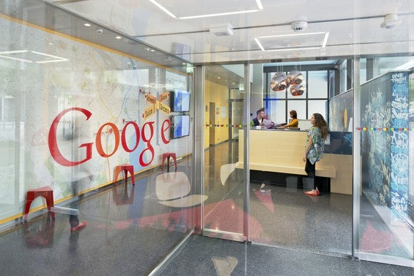 An entrance to an office with a glass wall and the Google logo.