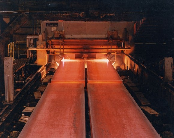 Hot steel sheets rolling out of oven furnaces along a conveyor belt.