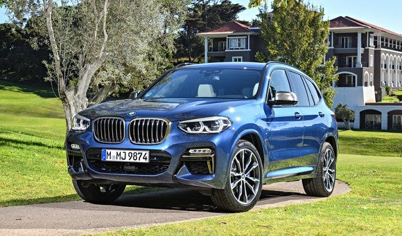 A blue BMW X3, a compact luxury crossover SUV, parked at an estate surrounded by green lawn