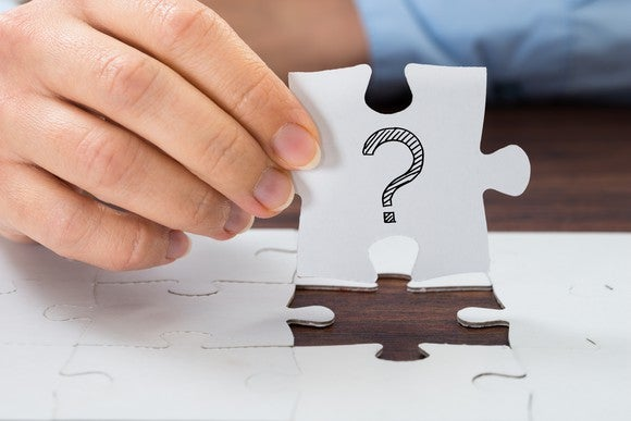 Handing holding a jigsaw puzzle piece with question mark drawn on it