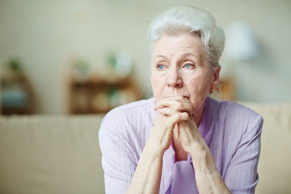 An older woman with her hands clasped in front of her and a worried look on her face.