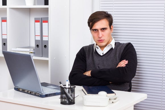 An annoyed millennial with his arms crossed in front of his laptop.