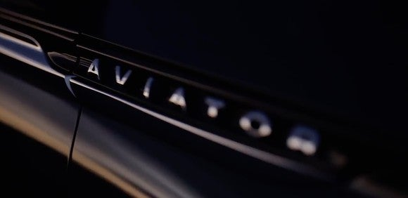 "A ""teaser"" image showing the Aviator logo visible on the side of a black vehicle."