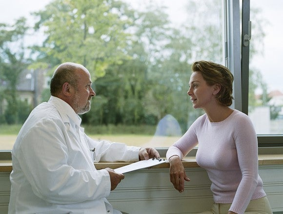 A medical professional in a white coat holding a clipboard and talking to a person.