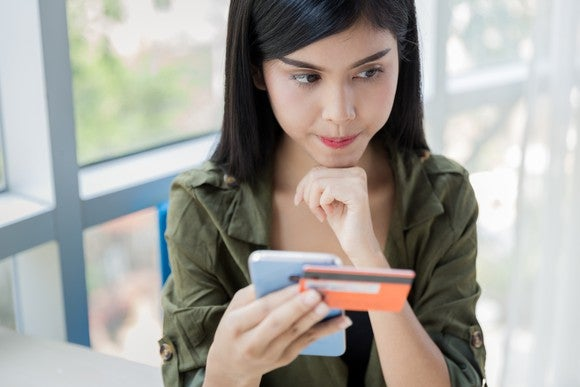 young woman resting chin on fist and holding smartphone and credit card