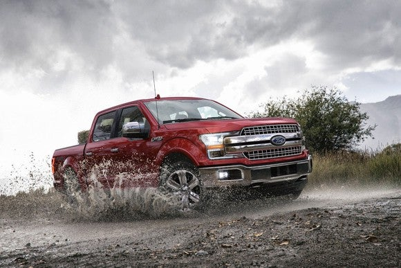 Ford F-150 Pickup driving on a muddy, wet, dirt road.