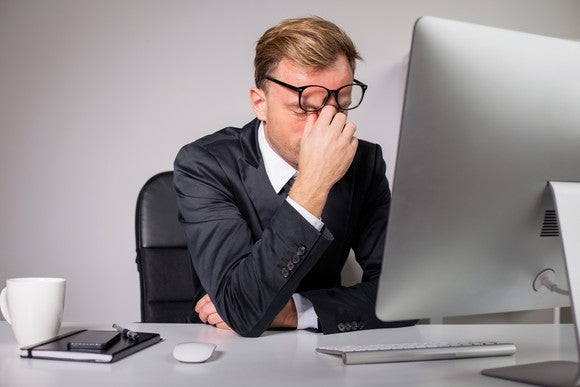 Man in suit with eyes closed while sitting at computer and right hand pinching forehead