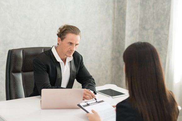 Man in suit looking stern, sitting across the desk from a woman.