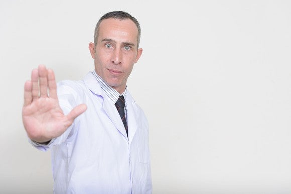 A man in a lab coat holds his hand up with the palm facing out