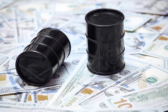 Two miniature oil barrels on top of U.S. currency.