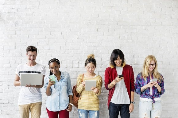 Five smiling young people using mobile devices.