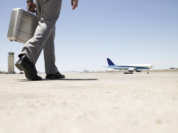 Man in grey suit pants and black shoes holding a briefcase and walking to an airplane
