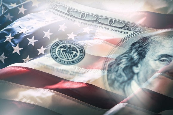 An American flag interposed with a $100 bill.