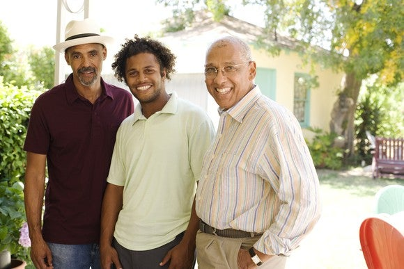 Three men standing next to each other and smiling in front of a house.