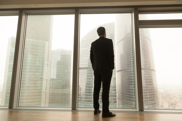 Businessman looking out window at skyscrapers