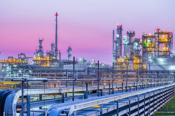 An oil refinery with a pink sky in the backdrop