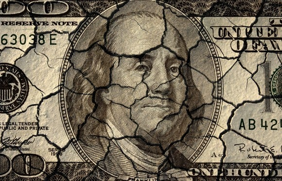 A $100 bill painted on a cracked and crumbling surface.