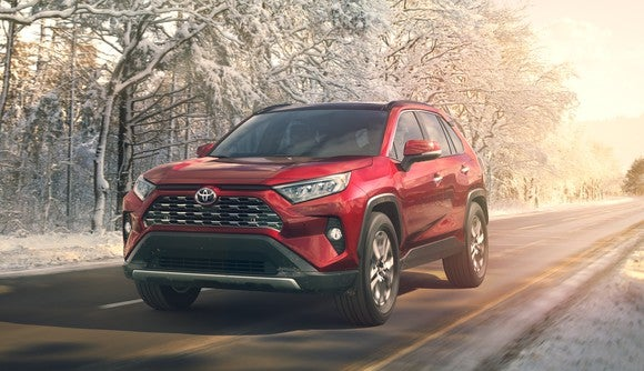 A red 2019 Toyota RAV4, a compact SUV, on a road next to a line of snow-covered trees.