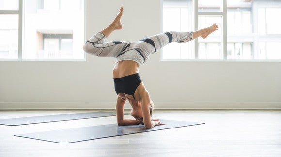 A woman wearing Lululemon apparel doing yoga in a bright room with large windows