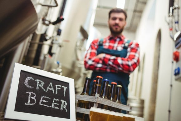 Craft brewer stands behind a six-pack of beer.
