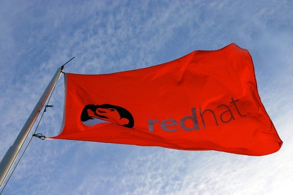 A red flag emblazoned with Red Hat's logo, fluttering in the wind.
