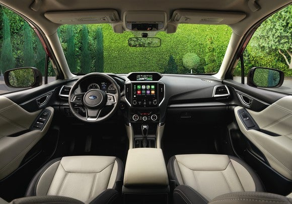 The front seats and dashboard of a 2019 Subaru Forester Touring, with two-tone leather seats and polished black and metal trims.