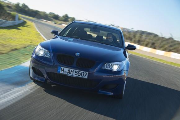 A dark blue BMW M5 on a European testing track.