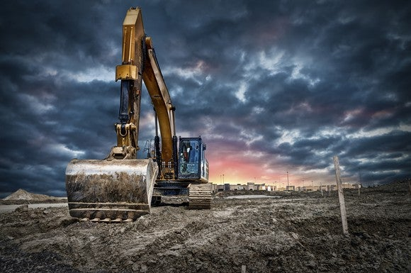 A backhoe on a construction site with a cloudy sky and setting sun