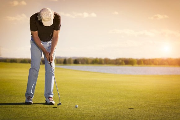 Man looking down at his golf club while playing on a golf course