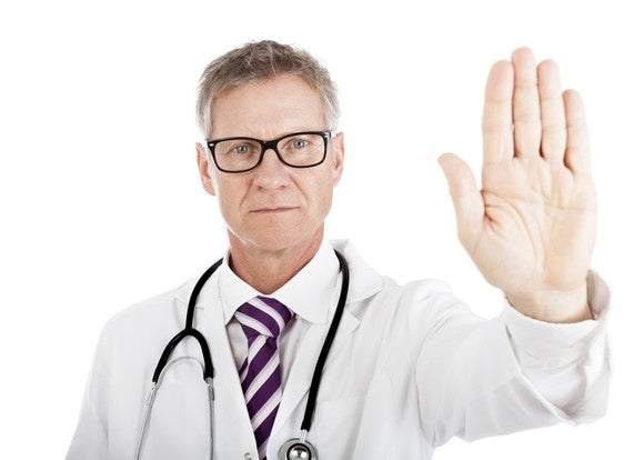 Man in lab coat holding up hand with palm facing outward