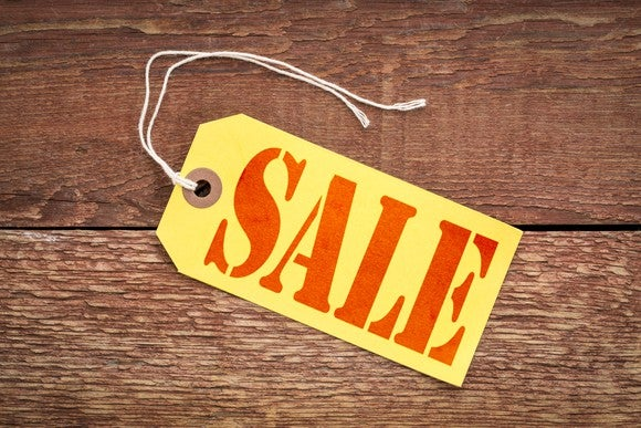 A sale sign on a yellow paper price tag against rustic wood.