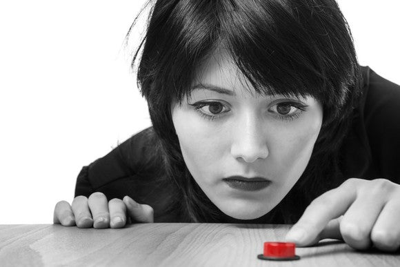 Close up studio shot of a young business model wearing a black blouse, ready to press a red button