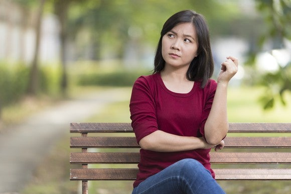 woman sitting on a bench looking confused or questioning