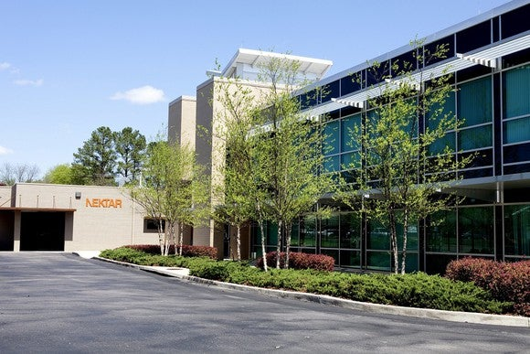 Two-story office building with landscaping and Nektar logo on wall.