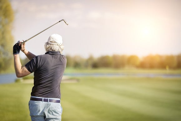 Senior golfer swinging club