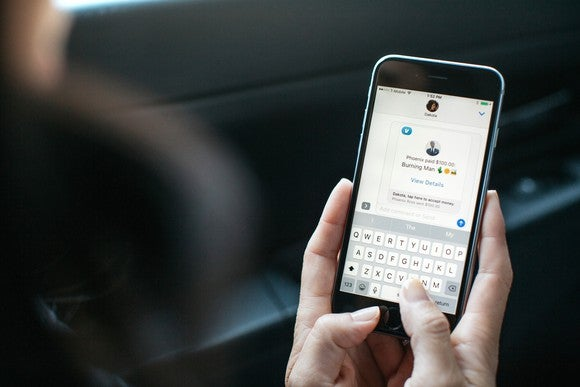 Two hands holding a smartphone typing a message into the Venmo app.
