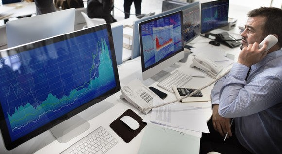 A stock trader looking at charts on his computer while on the phone.