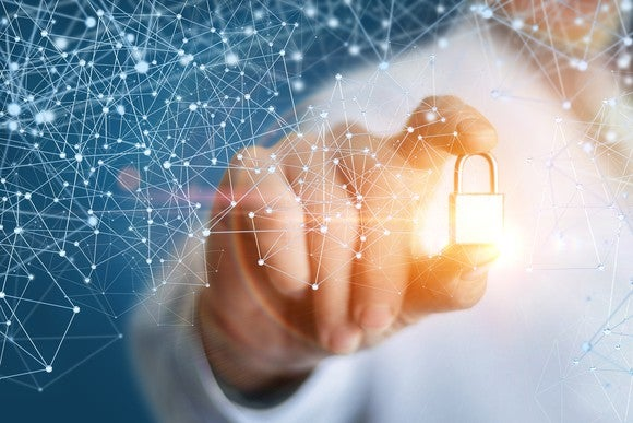 A person holding a glowing golden lock that's surrounded by latticework representing blockchain.