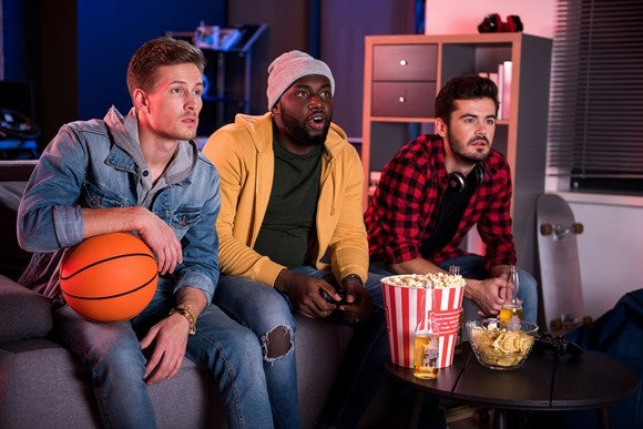 Three male fans sitting on a couch watching a game.