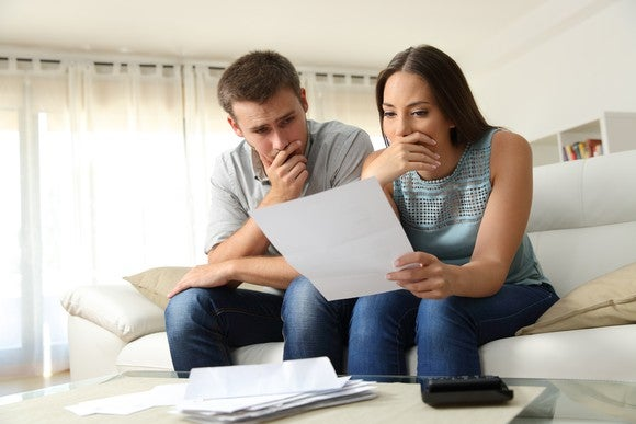 A couple looking at a bill with worried expressions