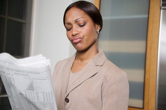 A businesswoman closely reading the financial section of a newspaper.