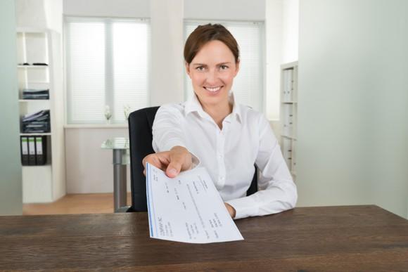 Businesswoman handing over a paycheck.