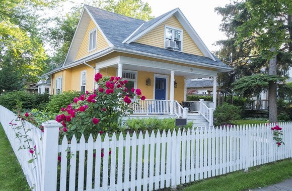 Yellow house with picket fence.